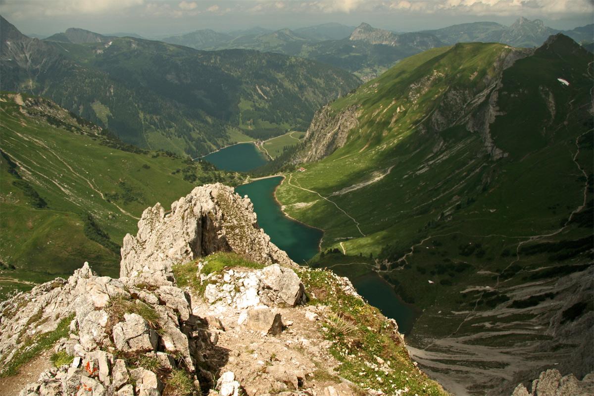 Gipfelblick von der Lachenspitze hinab zu den drei Seen der Lache, dem Traualp- und dem Vilsalpsee, im Hintergrund die Berge um Tannheim mit Schönkahler, Einstein und rechts der Aggenstein bei Grän