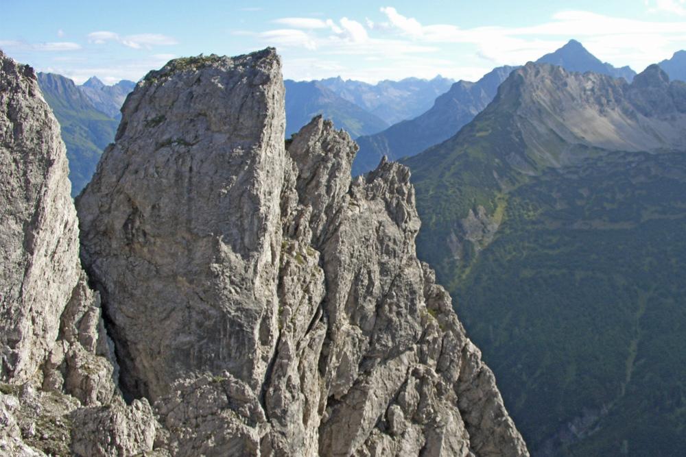 Ausblick aus einer gegen Süden ausgerichteten Rinne, über welche die Saldeinerspitze erstiegen werden kann; markante Felstürme flankieren die Rinne und im Hintergrund ist die Grubach- und Klimmspitze sichtbar