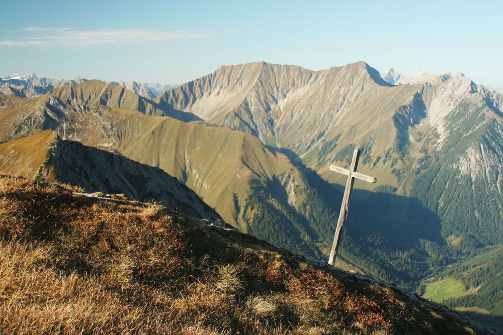 das kleine alte Gipfelkreuz am Sandegg, im Hintergrund der Kreuzspitzkamm mit dem Anhalter Höhenweg
