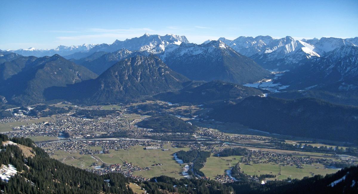 Gipfelblick von der Schneid hinab in das Reuttener Becken und zu den Ammergauer Alpen, im Hintergrund das Wettersteinmassiv