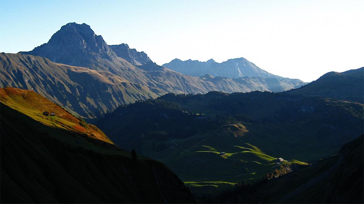 Blick hinab zu der im ersten Sonnenlicht liegenden Unteren Auenfeldalpe, im Hintergrund der Widderstein (li.) und das Walser Geißhorn