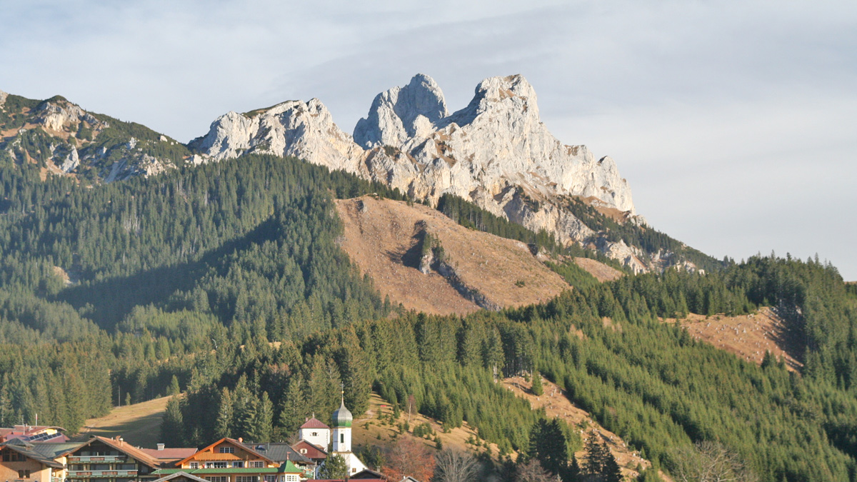 die Gräner Pfarrkirche ist dem heiligen Wendelin - dem Schutzpatron des Viehs - gewidmet - im Hintergrund die westlichen Felsberge der Tannheimer Gruppe (v.l.) Schartschrofen, Gimpel und Rote Flüh