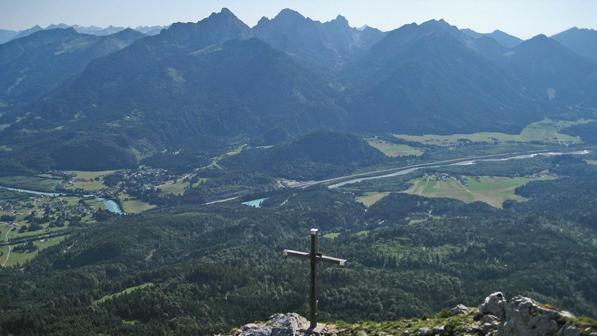 vom 'deutschen' Gipfelkreuz blickt man auf das etwas vorgeschobene österreichische Gipfelkreuz hinab - im Hintergrund schlängelt sich der Lech durch die Landschaft bei Pflach, Pinswang und Musau