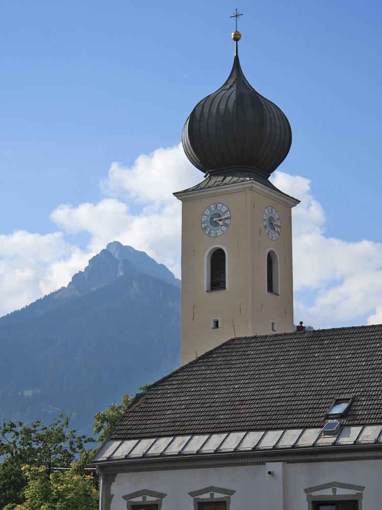 der Kirchturm der Reuttener Pfarrkirche Sankt Anna aus der Schulstraße gesehen - im Hintergrund die Gehrenspitze