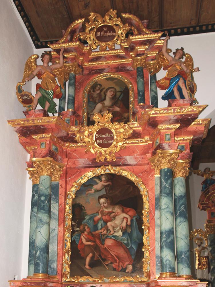 der linke Seitenaltar der Schöllanger Burgkirche mit der Gottesmutter Maria und dem Jesuskind, welches der Knabe Johannes gerade wachkitzeln möchte, stammt von dem Reuttener Maler Paul Zeiller (1707)
