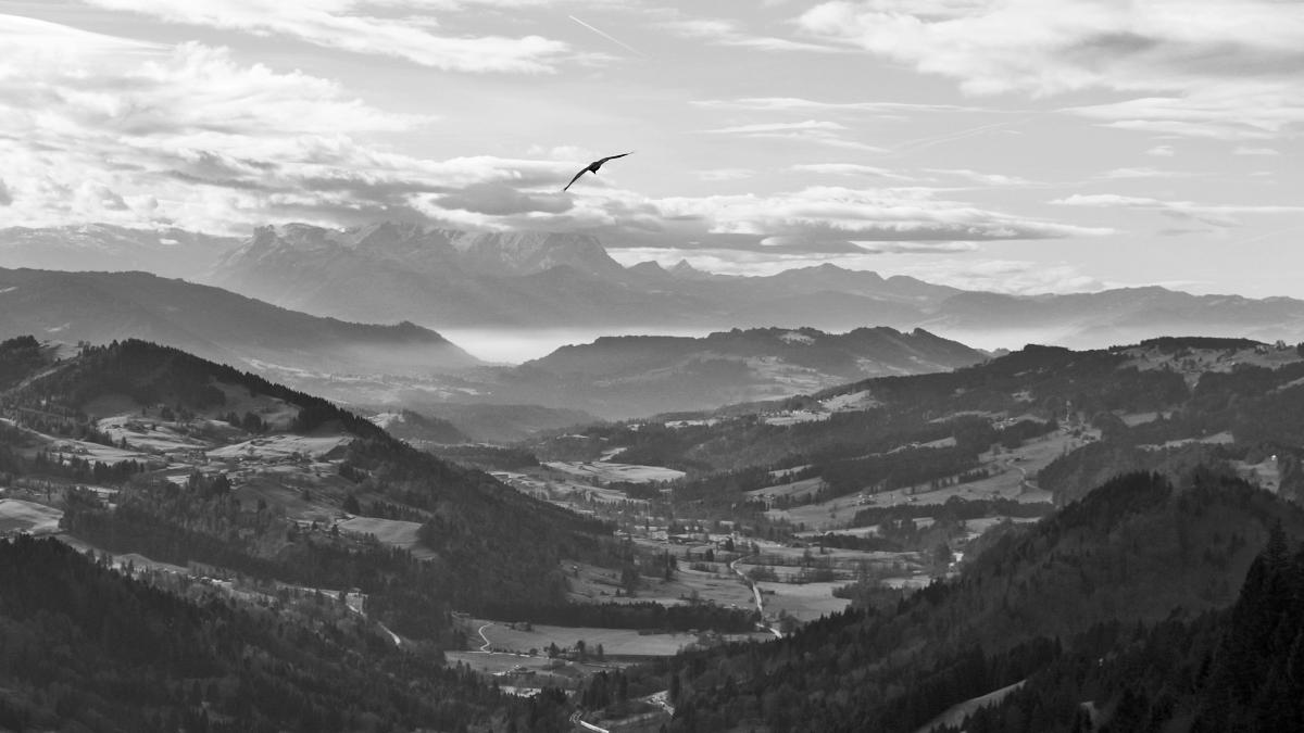 Ausblick von der Salmaser Höhe gegen Südwesten hinein in das Tal der Weißach und den dahinter aufragenden, aber von Wolken eingehüllten Schweizer Bergen