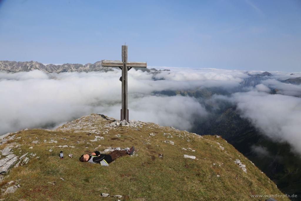 Rast am Gipfelkreuz vom Wiedemer Kopf über den Wolken