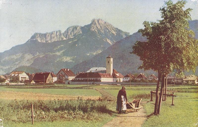 Reutte mit Säuling im Hintergrund und einer Frau mit Sackkarre vorne