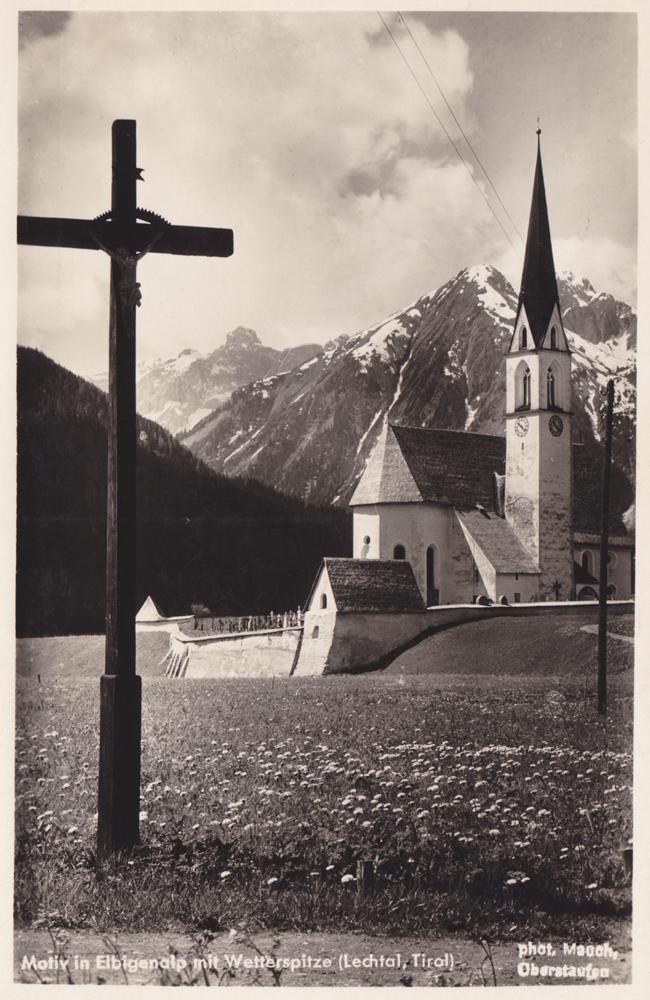 die St. Nikolaus-Kirche mit der vorgelagerten Martinskapelle in Elbigenalp - im Hintergrund die Holzgauer Wetterspitze - etwa 40er Jahre (Photogr. Hugo Mauch)